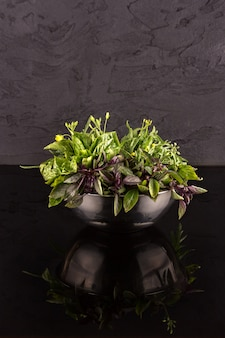 Bowl with greens on a black