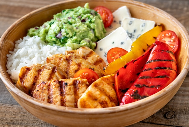 Bowl with grilled chicken, rice, blue cheese and vegetables