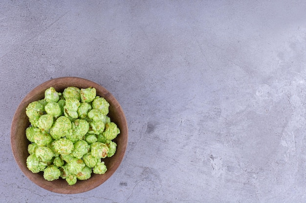 Ciotola con un mucchio di caramelle popcorn verdi su sfondo marmo. foto di alta qualità