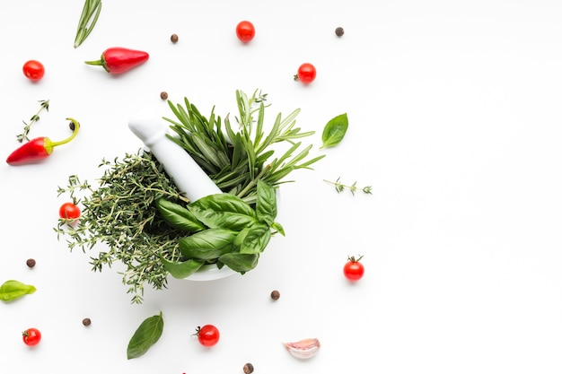Bowl with herbs surrounded by vegetables