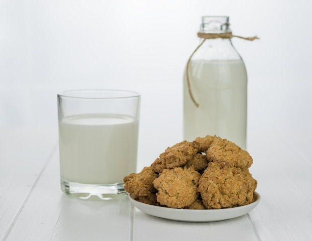 Bowl with homemade biscuits from flour and milk on a white wooden table.