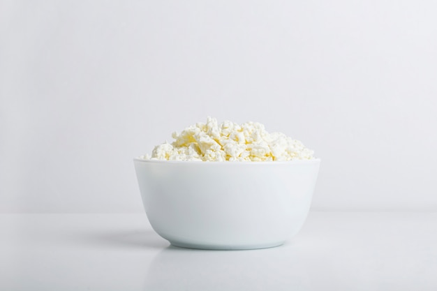 Bowl with homemade cottage cheese on a white background. concept of healthy dairy products with calcium. nutrition concept