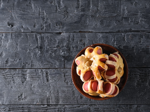 Bowl with homemade sausage rolls on a black table.