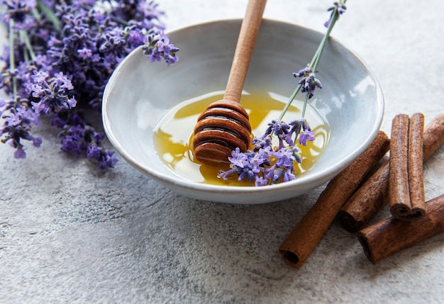 Bowl with honey and fresh lavender flowers on a concrete background