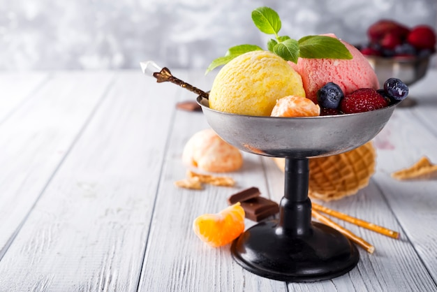 Bowl with ice cream with three different scoops of yellow, red colors and waffle cone