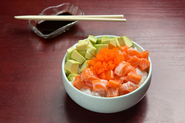 Bowl with japanese sushi, on wooden table.