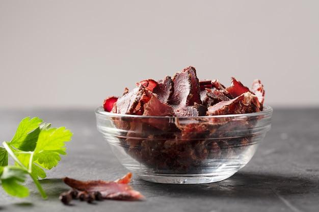 暗いテーブルの上にジャーキーの肉とパセリを入れたボウル、水平方向
