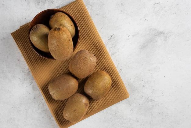 갈색 식탁보에 키위 과일 그릇