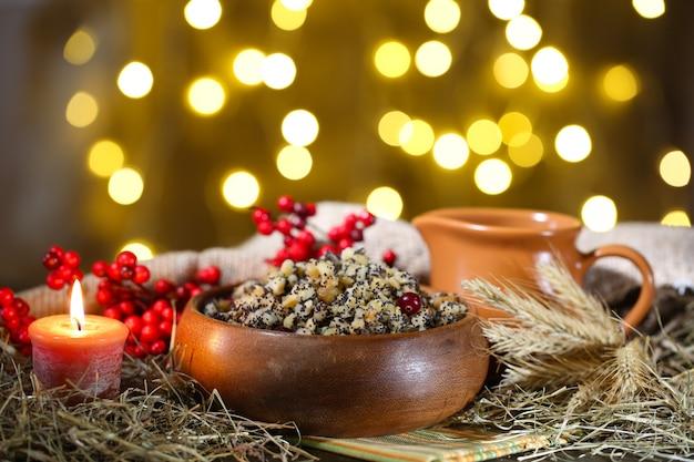 Чаша с кутьей - традиционная рождественская сладкая еда в украине, беларуси и польше, на деревянном столе, на ярком фоне