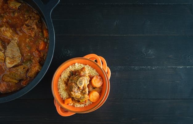 검은 나무 바탕에 야채와 쿠스쿠스를 곁들인 양고기 그릇. 라마단 개념입니다. 공간을 복사합니다. 평면도.