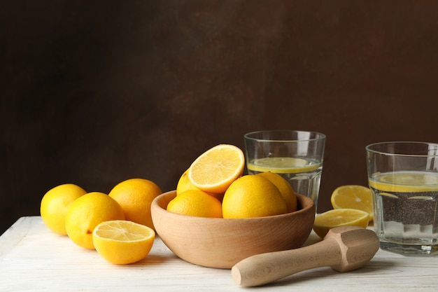Bowl with lemons, juicer and lemonade on wooden table