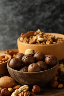 Bowl with macadamia and different nuts on wooden table