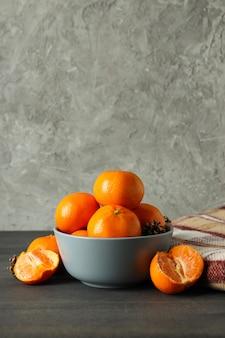 マンダリンと暗い木製のテーブルの上の格子縞のボウル