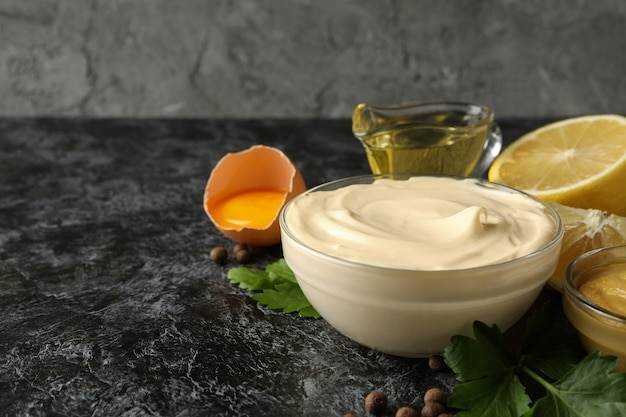 Bowl with mayonnaise and ingredients for cooking on black smokey background