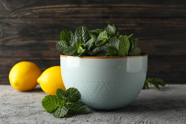 Bowl with mint and lemons on grey, close up