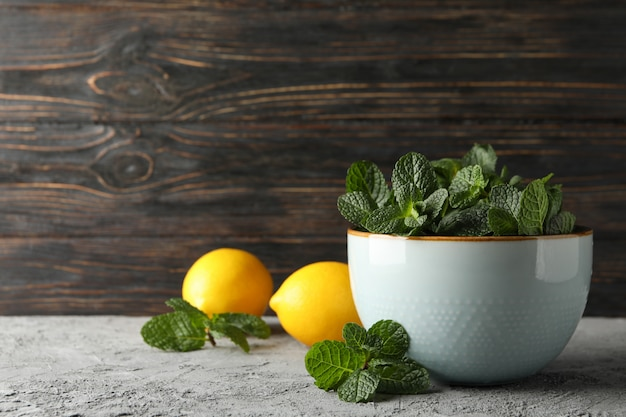 Bowl with mint and lemons on grey, space for text