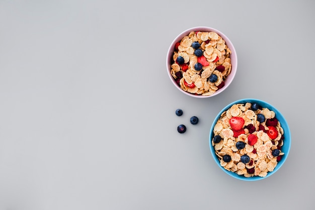 Bowl with muesli and blueberries on grey background with copyspace