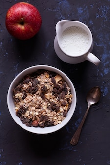 Bowl with muesli, jug of milk and red apple
