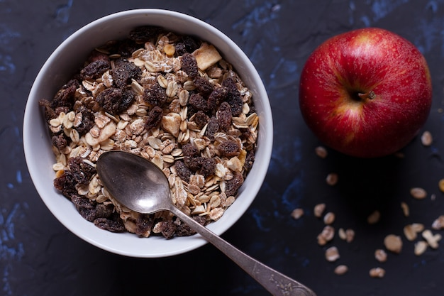 Bowl with muesli with a spoon, and an apple on a black background viewed from above.