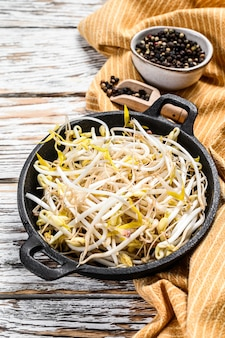 Bowl with mungbean sprouts on wooden background