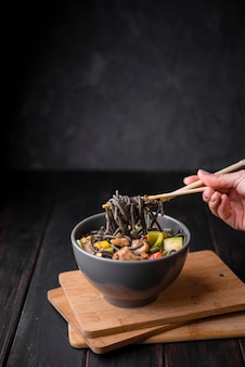 Bowl with noodles and chopsticks
