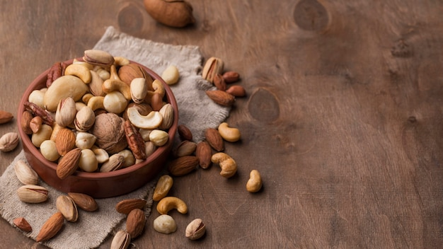 Bowl with nuts copy space wooden background