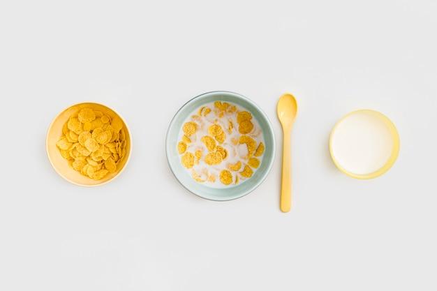コーンフレークと机の上のミルクのボウル
