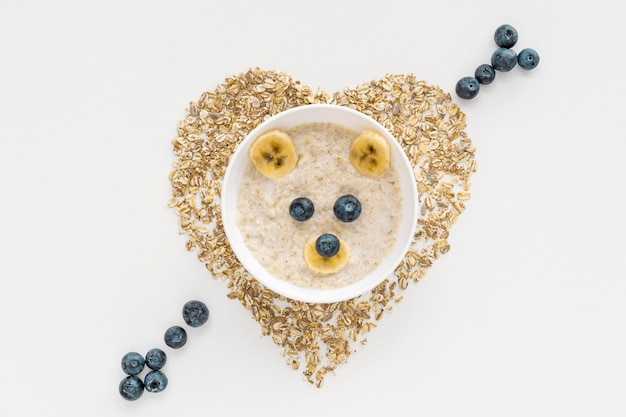Bowl with oat flakes and fruits with heart shape on table
