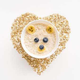 Bowl with oat flakes and fruits with heart shape