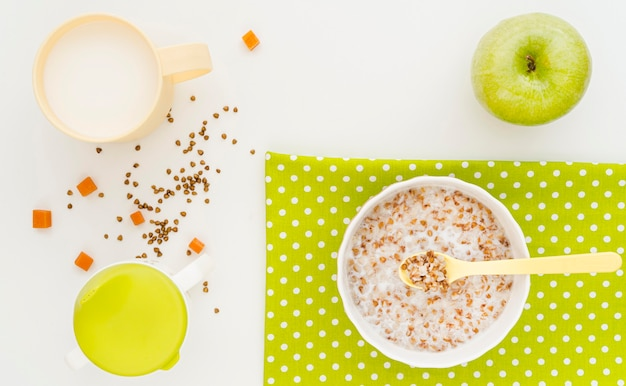 Bowl with oat flakes and glass of milk and apple