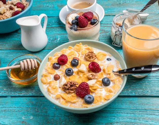 Bowl with oat flakes with raspberries and blueberries on a blue wooden table.