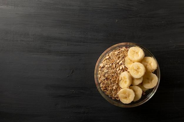 Чаша с овсяными зернами, стакан молока и банан на черном столе, концепция здорового завтрака, темная