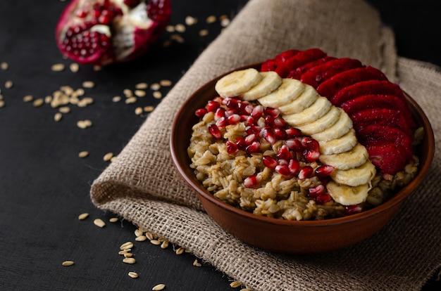 Bowl with oat porridge, banana, pomegranate seeds and opuntia cactus fruit