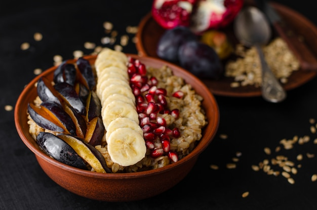 Bowl with oat porridge, banana, pomegranate seeds and plum
