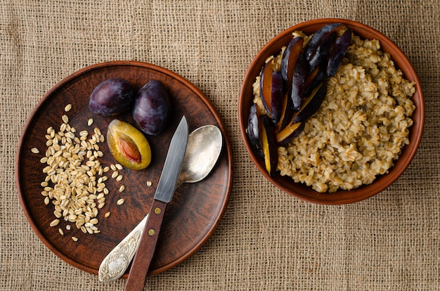 Bowl with oat porridge and plum on sackcloth