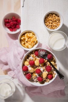 Bowl with oatmeal, corn flakes, raspberry and a glass of milk on a white wooden