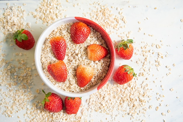 Bowl with oatmeal and strawberries around