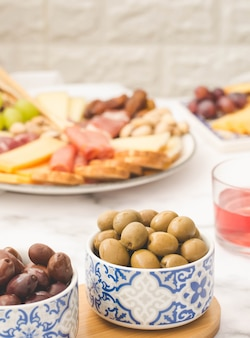 Bowl with olives accompanying a brunch consisting of a table of cheeses and sausages.