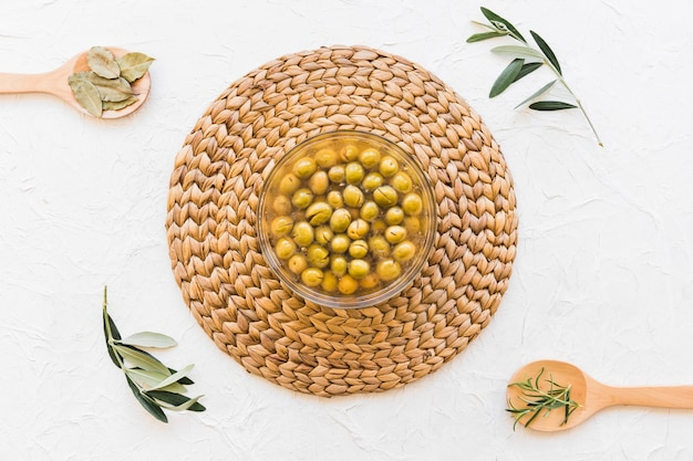 Bowl with olives and oil and herbs on white background