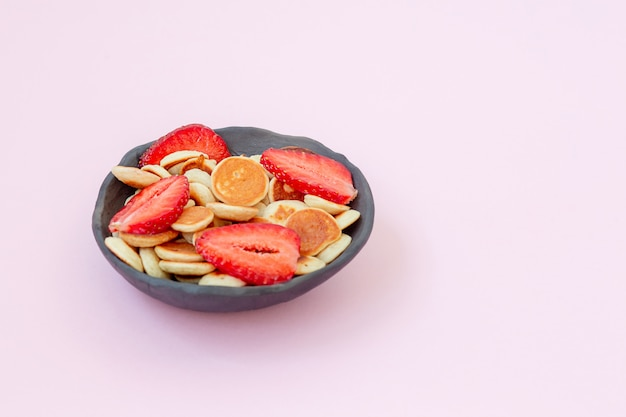 Bowl with pancake cereal with strawberry on ink background.