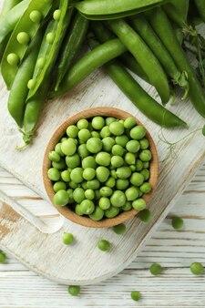 木製のエンドウ豆の種と新鮮なエンドウ豆のボウル