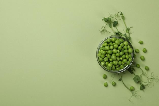 緑の背景にエンドウ豆の種子とボウル