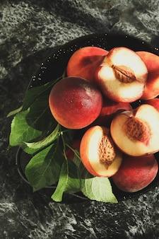 Чаша с фруктами персика на черном дымчатом столе