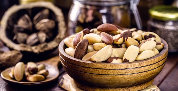 Чаша с очищенными бразильскими орехами на деревенском столе. здоровый кулинарный ингредиент