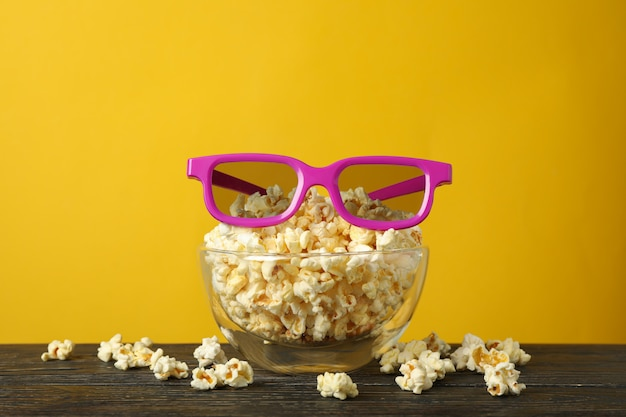 Bowl with popcorn and 3d glasses on wooden table. food for watching cinema