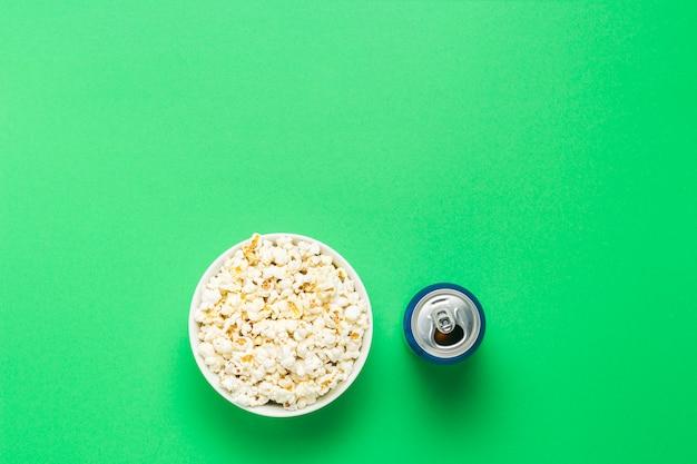 팝콘과 녹색 배경에 음료 수있는 그릇. 영화와 좋아하는 tv 쇼, 스포츠 경기를 보는 개념. 평평한 누워, 평면도.