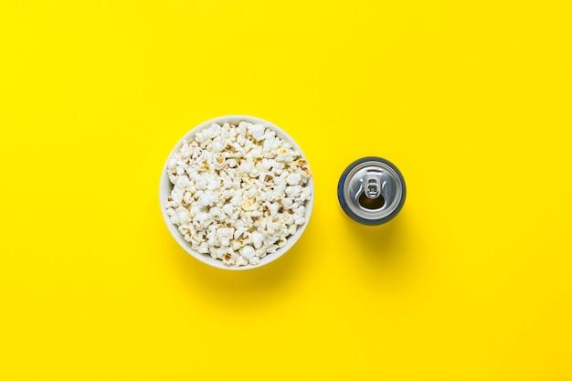 팝콘 그릇과 노란색 배경에 음료와 함께 수 있습니다. 영화와 좋아하는 tv 쇼, 스포츠 경기를 보는 개념. 평평한 누워, 평면도.