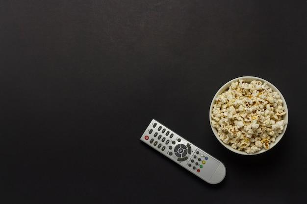 Чаша с попкорном и тв пульт на черном фоне. концепция просмотра тв, кино, сериалов, спортивных передач, шоу. плоская планировка, вид сверху.