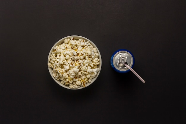 Bowl with popcorn and a can of drink on a black background. the concept of watching movies and favorite tv shows, sports competitions. flat lay, top view.