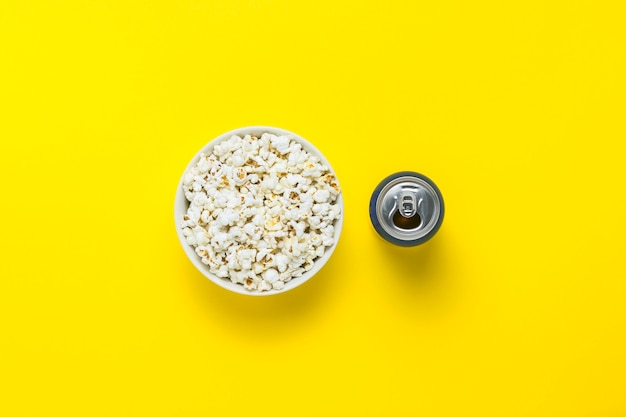 Bowl with popcorn and a can with a drink on a yellow background. the concept of watching movies and favorite tv shows, sports competitions. flat lay, top view.